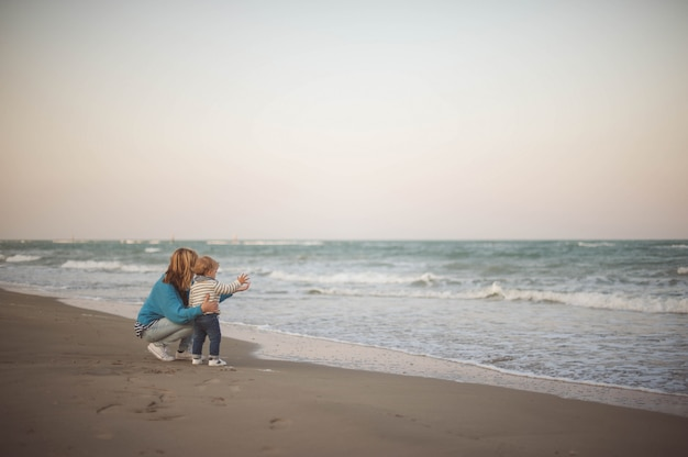 Woman embracing her son while looking at the sea Premium Photo