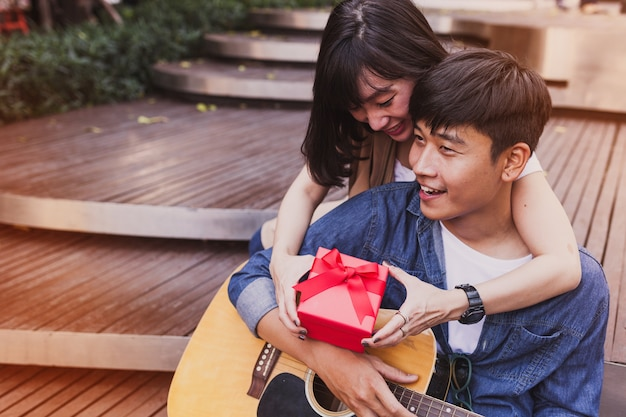 Woman embracing a man and holding a gift while he plays the guitar Free Photo