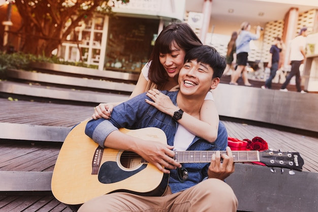 Woman embracing a man while he plays guitar Free Photo