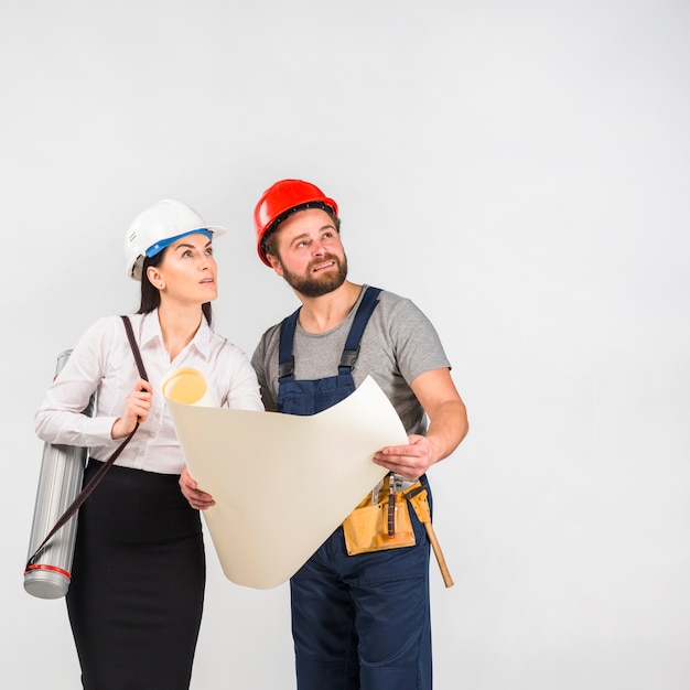 Woman engineer and builder discussing project looking up Free Photo