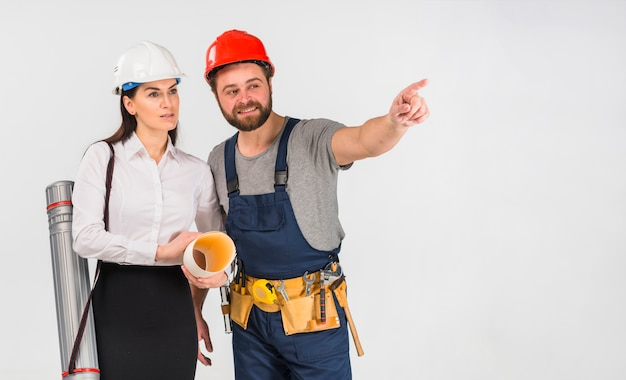 Woman engineer and builder pointing away Free Photo