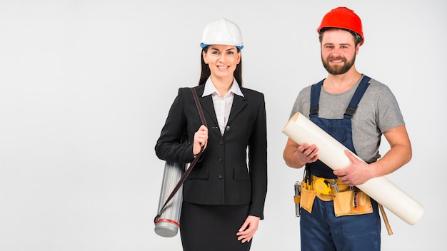 Woman engineer and builder standing with whatman smiling Free Photo