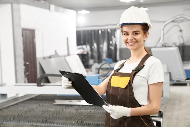 Ingegnere della donna in casco e tute in posa in fabbrica. Foto Gratuite