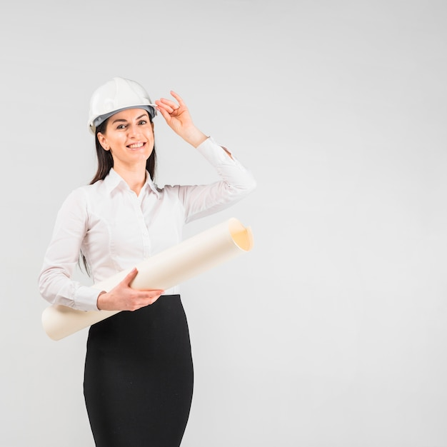 Woman engineer in helmet with whatman paper roll Free Photo