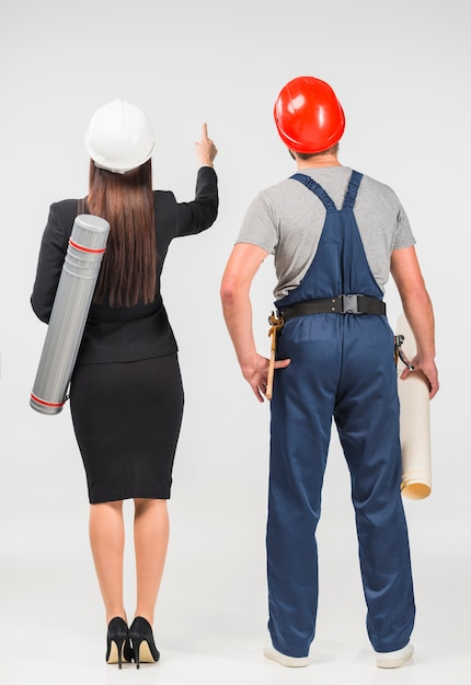 Woman engineer standing with builder pointing up Free Photo