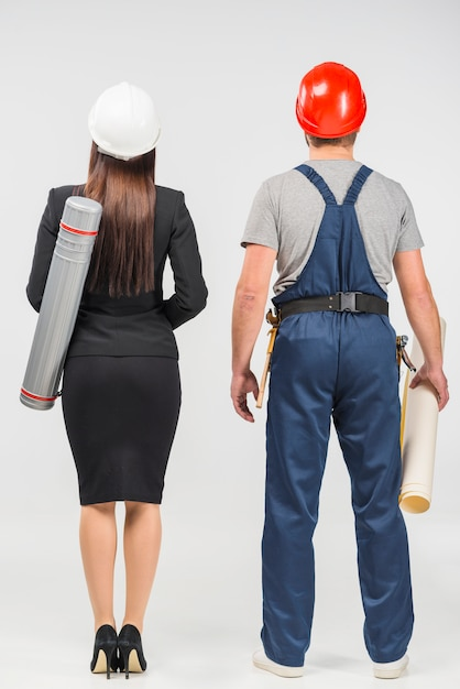 Woman engineer in suit standing with builder Free Photo