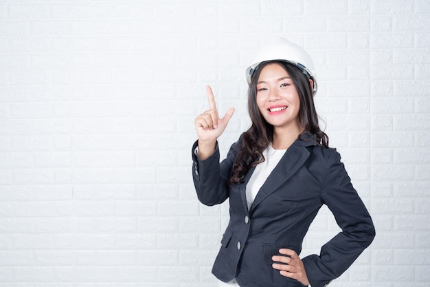 Woman of engineering holding a hat, separate the white brick wall made gestures with sign language. Free Photo