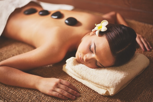 Woman enjoying a stone massage Free Photo