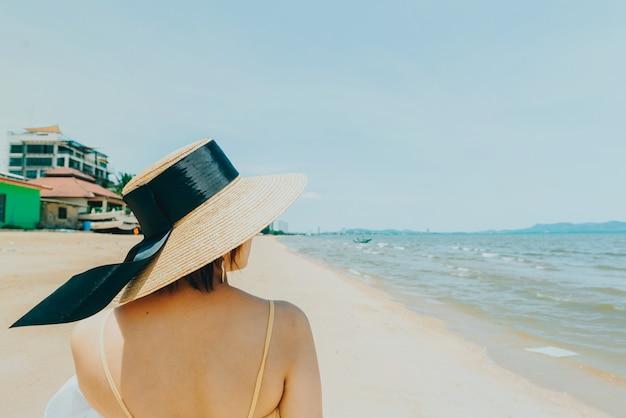 Woman enjoying beach relaxing joyful in summer by tropical blue water. Premium Photo