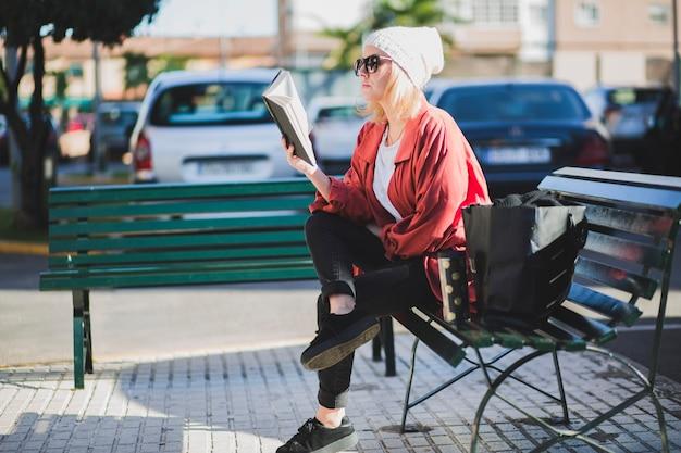 Woman enjoying book on street Free Photo