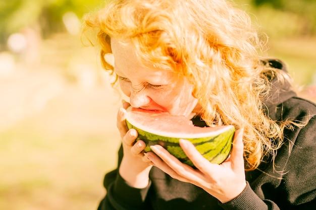 Woman enjoying fresh juicy watermelon in daylight Free Photo