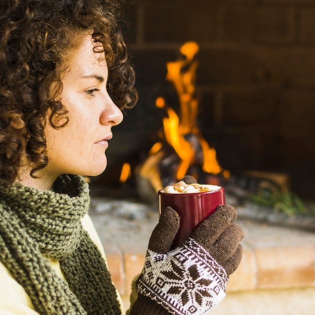 Woman enjoying hot beverage near fireplace Free Photo