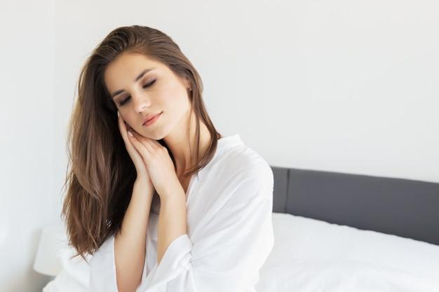Woman enjoying morning awakening in a soft snow-white bed. Premium Photo