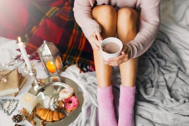 Женщина наслаждается утренним временем в своей постели, одетая в теплый уютный шерстяной свитер и розовые носки, держа большую чашку кофе. Бесплатные Фотографии