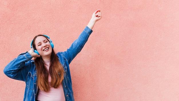 Женщина, наслаждаясь музыкой в наушниках с копией пространства Premium Фотографии