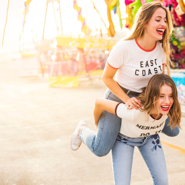 Woman enjoying piggyback ride at amusement park Free Photo