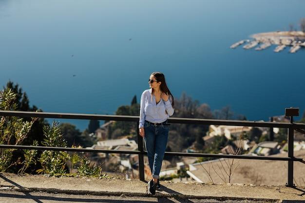 ルガーノのサンサルヴァトーレ山からルガーノ湖の美しい景色を楽しむ女性 Premium写真