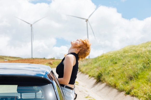 Woman enjoying sun out of car window on bright day Free Photo