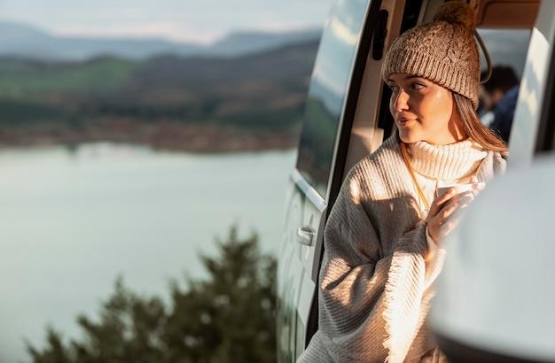 ロードトリップ中に車から自然の景色を楽しむ女性 無料写真