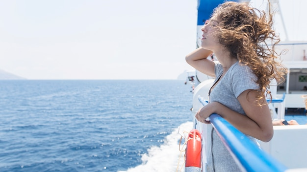 Woman enjoying travelling in cruise overlooking the sea Free Photo
