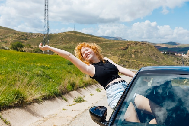 Woman enjoying trip out of car window and stretching out arm with closed eyes Free Photo