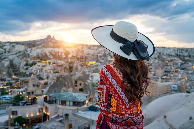 トルコのカッパドキア、ギョレメの町の景色を楽しむ女性。 無料写真
