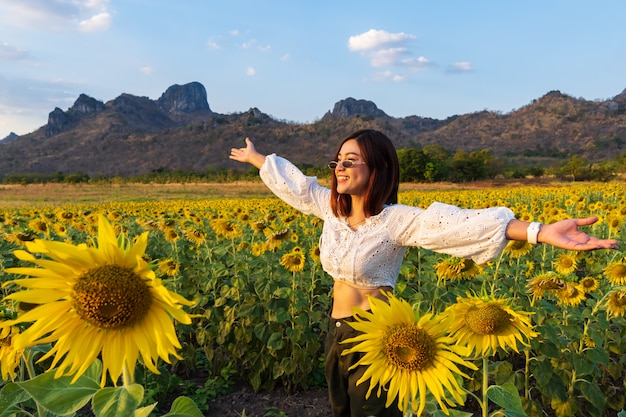 Woman enjoying with sunflower field at kao jeen lae in lopburi, thailand Premium Photo
