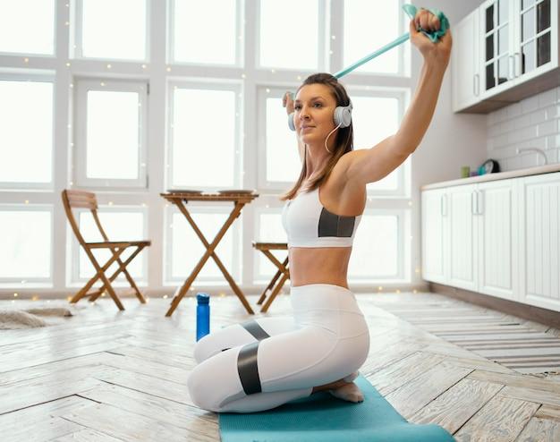 音楽を聴きながら家で運動する女性 無料写真