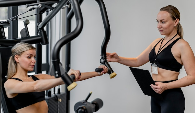 ジムで運動している女性とクリップボードを保持しているコーチ 無料写真
