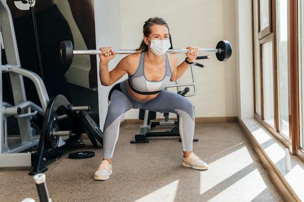 Женщина тренируется в тренажерном зале с оборудованием и медицинской маской Бесплатные Фотографии