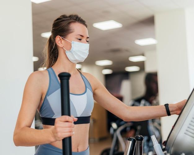 Женщина, тренирующаяся в тренажерном зале с маской Бесплатные Фотографии