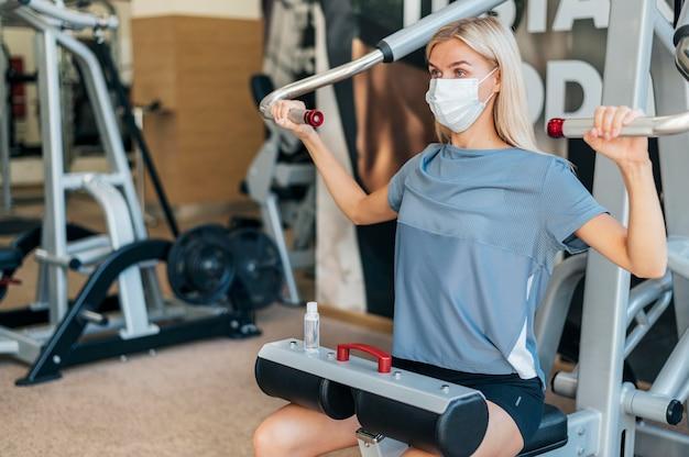 Женщина тренируется в тренажерном зале с медицинской маской и оборудованием Бесплатные Фотографии