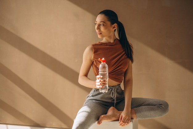Woman exercising and drinking water Free Photo