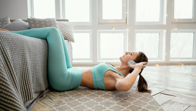 Woman exercising on mat and listening music Free Photo