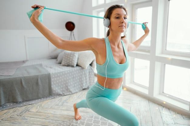 Женщина тренируется на коврике с резинкой Бесплатные Фотографии