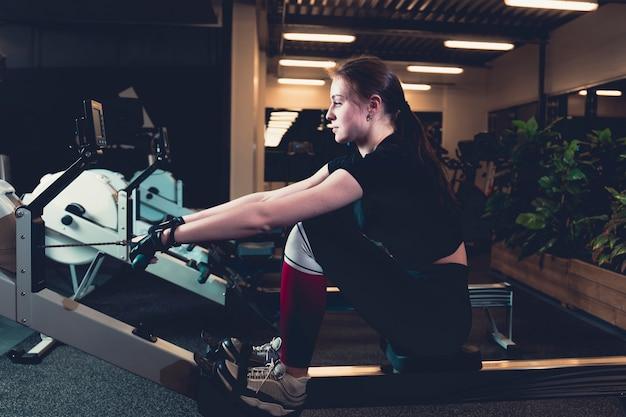 Woman exercising on rowing machine at gym Free Photo
