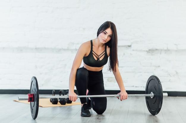 Женщина, тренирующаяся со штангой в фитнес-классе современного тренажерного зала на чердаке Premium Фотографии