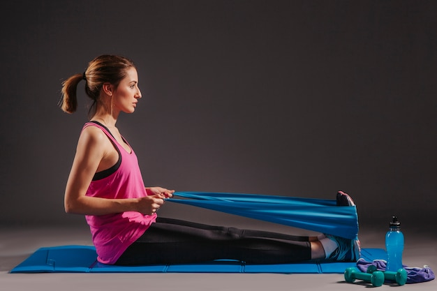 Woman exercising with elastic band on mat Free Photo