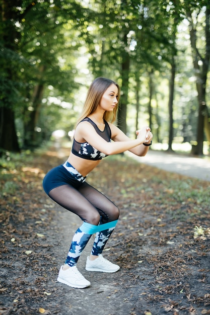 Woman exercising with elastic resistance band in the park Free Photo