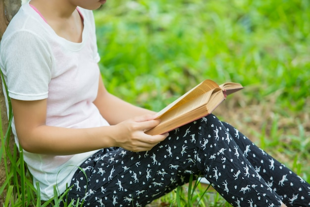Woman in eyeglasses reading book in park Premium Photo