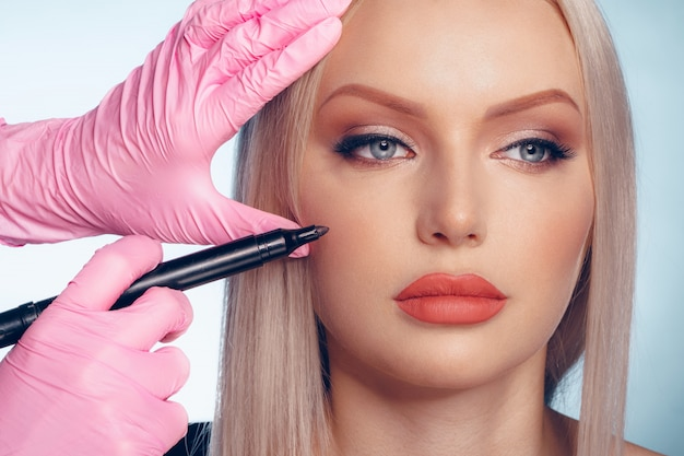 Woman face and doctor hands with pencil. plastic surgery Premium Photo