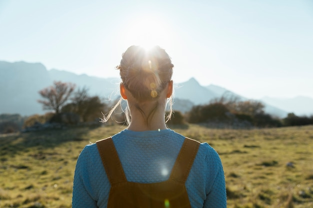 Woman facing sun in nature Free Photo
