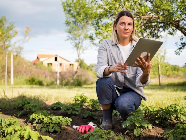 Woman farmer checking her garden with a tablet Free Photo