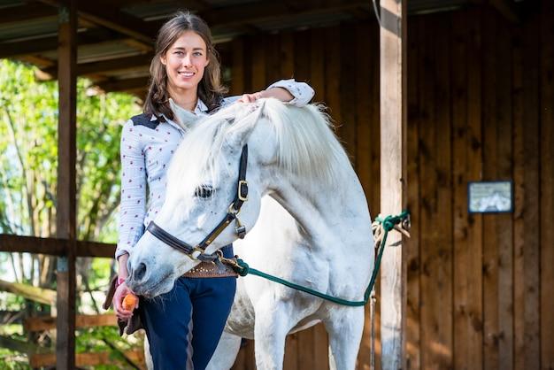 ニンジンを馬に給餌する女性 Premium写真