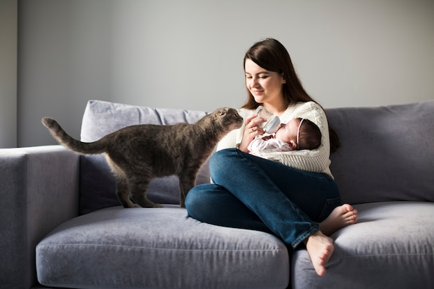 Woman feeding child on couch Free Photo