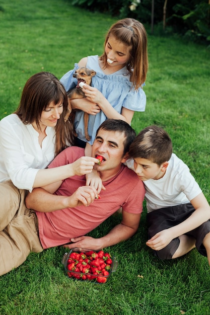 Woman feeding strawberry to husband while sitting with her children on grass Free Photo