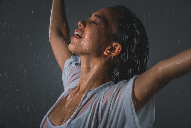 夏の雨の下で気分が良くて自由な女性 Premium写真