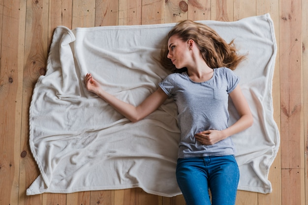 Woman feeling lonely while lying alone on plaid Free Photo