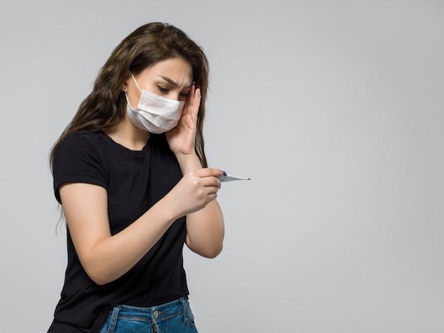 Donna che si sente preoccupata dopo aver esaminato un termometro Foto Gratuite