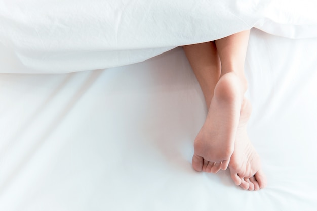 Woman feet on the bed under white blanket. sleeping and relax concept Premium Photo